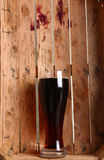 Dark ale in wooden crate Stock Images