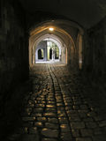 Dark alley in Armenien monastery. Dark alley in a monastery ,undre old arches ,leading to the light entrance Royalty Free Stock Images