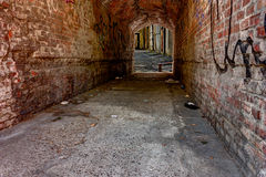 Dark alley. Dirty underpass in the old town  - dark, narrow grunge alley in the ghetto - squalid old passage in the slums of the city Stock Photo