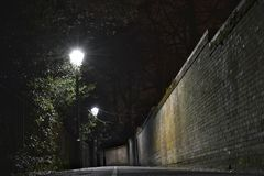 Dark alley night. Dark alley at night in London with street lights on, brick wall on one side and trees on other Royalty Free Stock Images