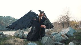 Dark angel of death with strong black feather wings and horns came down from heaven, harbinger of death, girl in