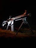 Dark AR-15. AR-15 with a handgun configuration on green netting in a dark scene Stock Photography