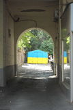 Dark arch into the courtyard with the light at the end of the arch. Background symbol of Ukrainian flag Stock Photography