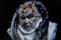Dark arts concept. Senior man with white beard dressed like monster. Demon on black background, close up. Man with royalty free stock image