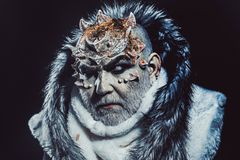 Dark arts concept. Senior man with white beard dressed like monster. Demon on black background, close up. Man with stock image