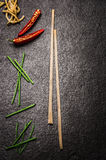 Dark asian food background with chopstick, chili and noodles Royalty Free Stock Image