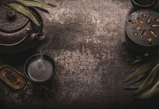 Dark asian tea background with black iron teapot and mug of green tea. Copy space for your design. Authentic vintage style. Traditional tea ceremony stock photography