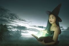 Dark asian witch woman with spell book royalty free stock photography