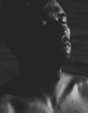 Dark atmospheric portrait of a relaxed man. Dark atmospheric portrait of a relaxed young man with a goatee with his head tilted back and eyes closed in Royalty Free Stock Image