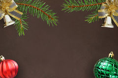 Dark background with branches of spruce, Christmas decorative bells, red wavy and green ball Royalty Free Stock Photography