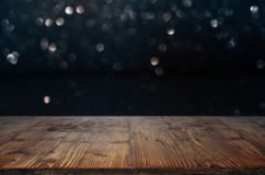 Dark bokeh background with wooden table stock image