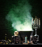 A dark background with candles and a skull Stock Photo