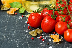Dark background with cherry tomatoes and ingredients Royalty Free Stock Photos