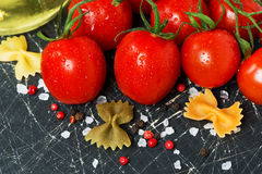 Dark background with cherry tomatoes and ingredients Royalty Free Stock Photography