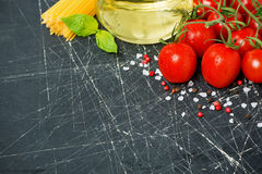 Dark background with cherry tomatoes, pasta, basil and olive oil Stock Photo