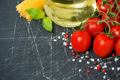 Dark background with cherry tomatoes, pasta, fresh basil Royalty Free Stock Images