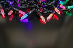 Christmas garland. On a dark background the colored lights of a Christmas tree garland. Blue, red, green colors. Festive decoration Royalty Free Stock Photos