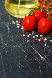 Dark background with fresh cherry tomatoes and olive oil Royalty Free Stock Photos