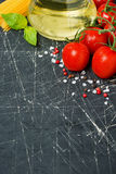Dark background with fresh cherry tomatoes, pasta and olive oil Stock Photo
