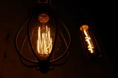 Dark background with glass retro-bulb Edison. Wallpapers with designer lamp of Edison. Designer light and lighting in interiors. stock photos