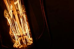 Dark background with glass retro-bulb Edison. Wallpapers with designer lamp of Edison. Designer light and lighting in interiors. stock photography