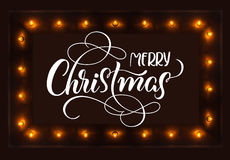 Dark background with light bulbs and Merry Christmas text. Calligraphy lettering Royalty Free Stock Photography
