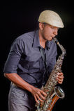 In a dark background man playing his saxophone, passion music Stock Photos