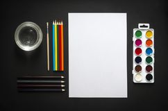On dark background paint sheet brush pencils colored jar with water horizontal top view flat lay background knolling Stock Image