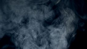 Dark background and puffs of mist floating and dissolving. 4K stock footage