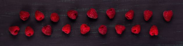 Dark background with red raspberries scattered in a line Royalty Free Stock Images