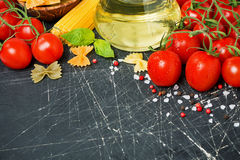 Dark background with tomatoes and ingredients Royalty Free Stock Image