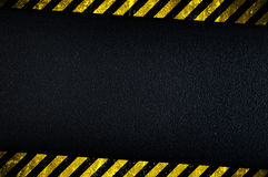 Dark background with yellow caution stripes. Grainy dark background with yellow caution stripes royalty free stock images