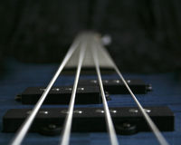 Dark Bass. Low key, narrow DOF view from the bridge of an electric bass guitar up the neck Royalty Free Stock Photo