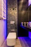Dark bathroom lightened with blue lights Stock Photos