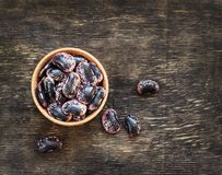 Dark beans on a dark wooden background in a cup royalty free stock photography