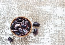 Dark beans on a light background in a wooden cup royalty free stock photos