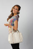 Dark beautiful girl in a trendy style with a white bag. Royalty Free Stock Image