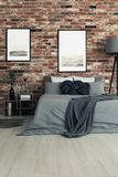 Dark bedding on king-size bed. In bedroom with gallery on brick wall and vase on nightstand Royalty Free Stock Photos