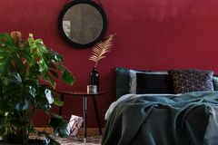 Dark bedroom interior with mirror. Round mirror on red wall above a table with gold leaf in dark bedroom interior with green bed royalty free stock photos