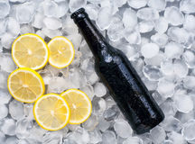 Dark beer bottle with lemon slices in the ice. Top view Stock Images