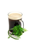 Dark beer in glass and bouquet of false shamrock Royalty Free Stock Photography