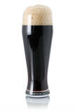 Dark beer in glass with foam royalty free stock photography