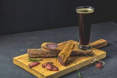 Dark beer in glass and Jerky, basturma, dried meat beef royalty free stock photography