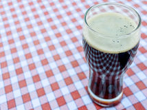 Dark beer in a glass on a red and white tablecloth Royalty Free Stock Photo