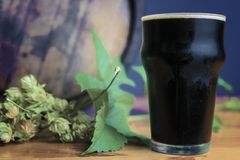 Glass of stout on a wooden table with leaves of hop against the background of barrels royalty free stock image