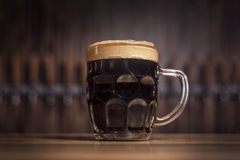 Dark beer in a large beer mug stands on the bar. Against the background of the taps Royalty Free Stock Photography