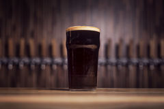 Dark beer in a large beer mug stands on the bar. Against the background of the taps Royalty Free Stock Image