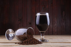 Dark beer and malt. Glass of dark beer and some roasted malt over a wooden background stock image