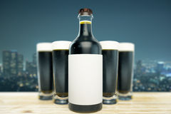 Dark beer mockup. Close up of dark beer bottle with blank label and full glasses on night city background. Ad concept. Mock up, 3D Rendering Royalty Free Stock Images