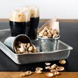 Dark beer and pistachios Stock Photo